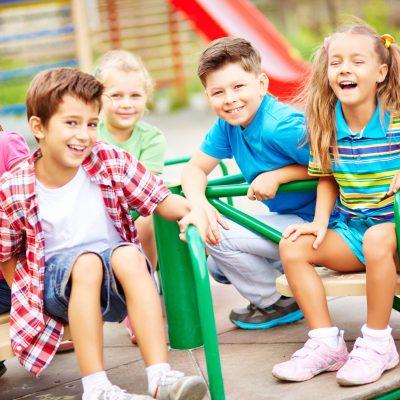 Image of joyful friends having fun on carousel outdoors